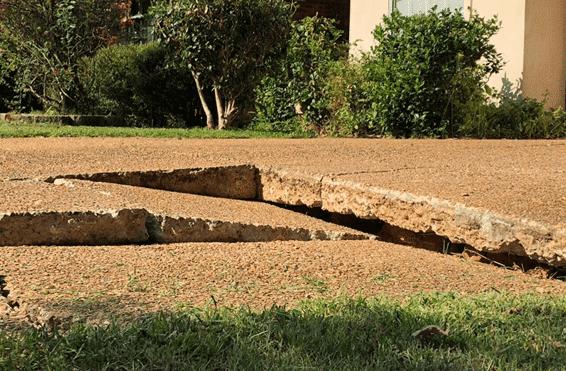 cracked and broken uneven concrete driveway