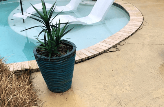 A pool deck. The concrete on the edge is cracked and uneven.